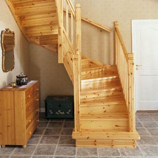 Bilden visar en U-svängd trappa, helt i klarlackad furu och med täta steg.