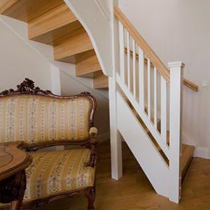 På bilden en vänstersvängd tät trappa med plan- och sättsteg, handledare samt överliggare i lackad massiv ek. Sidostycken, stolpar och räckespinnar täckmålade.